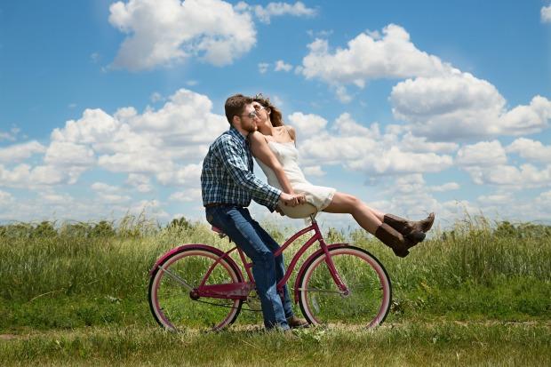 Una pareja heterosexual muy atractiva va en bici por el campo en un día soleado.