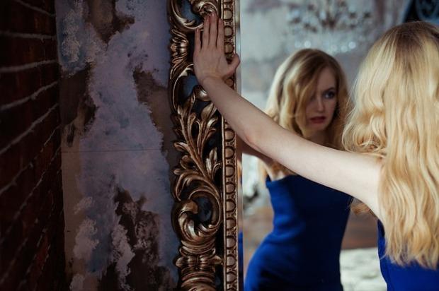 Una mujer se mira en el espejo, de forma que es al mismo tiempo quien mira y quien es mirada