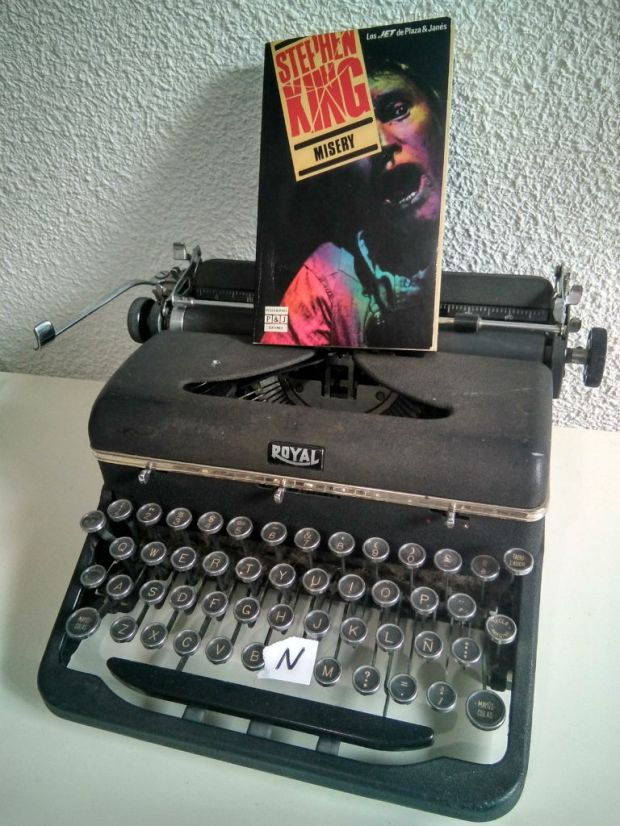 """Libro Misery de Stephen King sobre una máquina de escribir """"Royal"""", sin la letra N en su teclado."""
