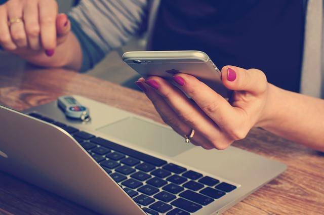 Una mujer teletrabaja en casa con su ordenador portátil y su teléfono móvil de empresa.