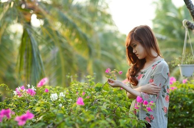 Una mujer joven reflexiona sobre sus problemas mientras mira unas flores