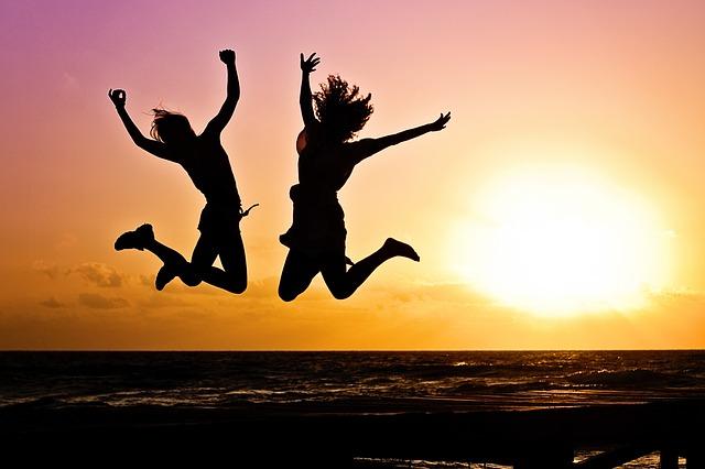 Dos tipos de persona saltan con un fondo de un atardecer en la playa, de manera que se ve su silueta.