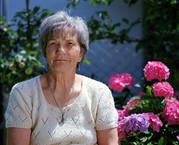 Una mujer mayor sentada en un jardín con hortensias