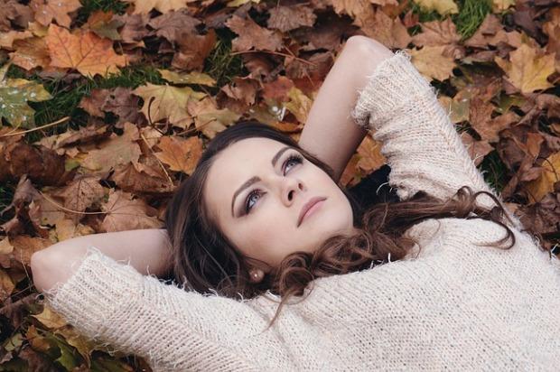 Mujer tumbada sobre hojas secas en un parque recordando el pasado