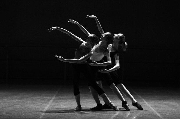 Tres bailarinas permanecen en una postura de ballet contemporáneo