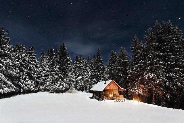 Cabaña con luz encendida en un bosque nevado al anochecer
