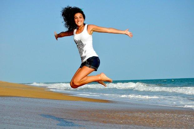 Una chica da un salto en una playa, ella está muy alegre, sonríe