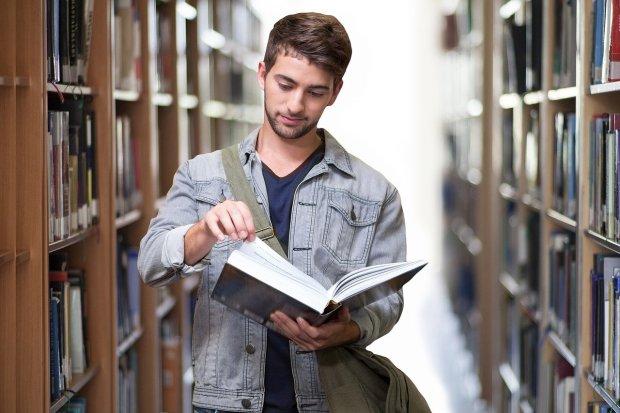Un estudiante recorre una biblioteca con un libro en la mano