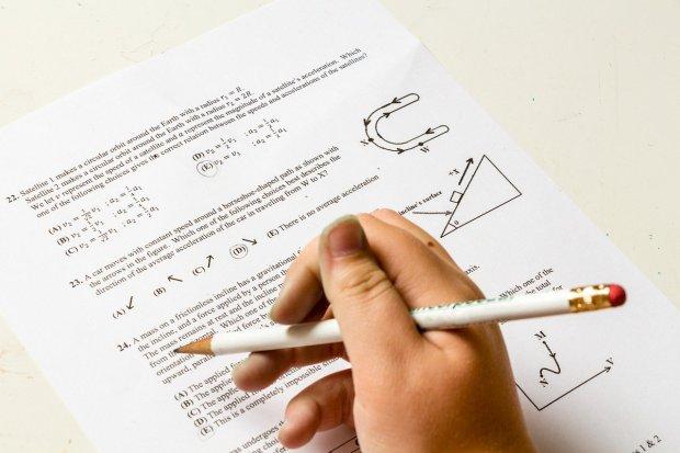 Imagen de una hoja de examen de matemáticas y una mano con un lápiz como resolviéndolo