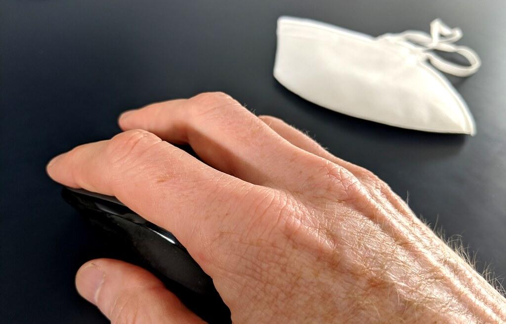Una mano de un alumno mueve el ratón mientras deja su mascarila FFP2 sobre la mesa.