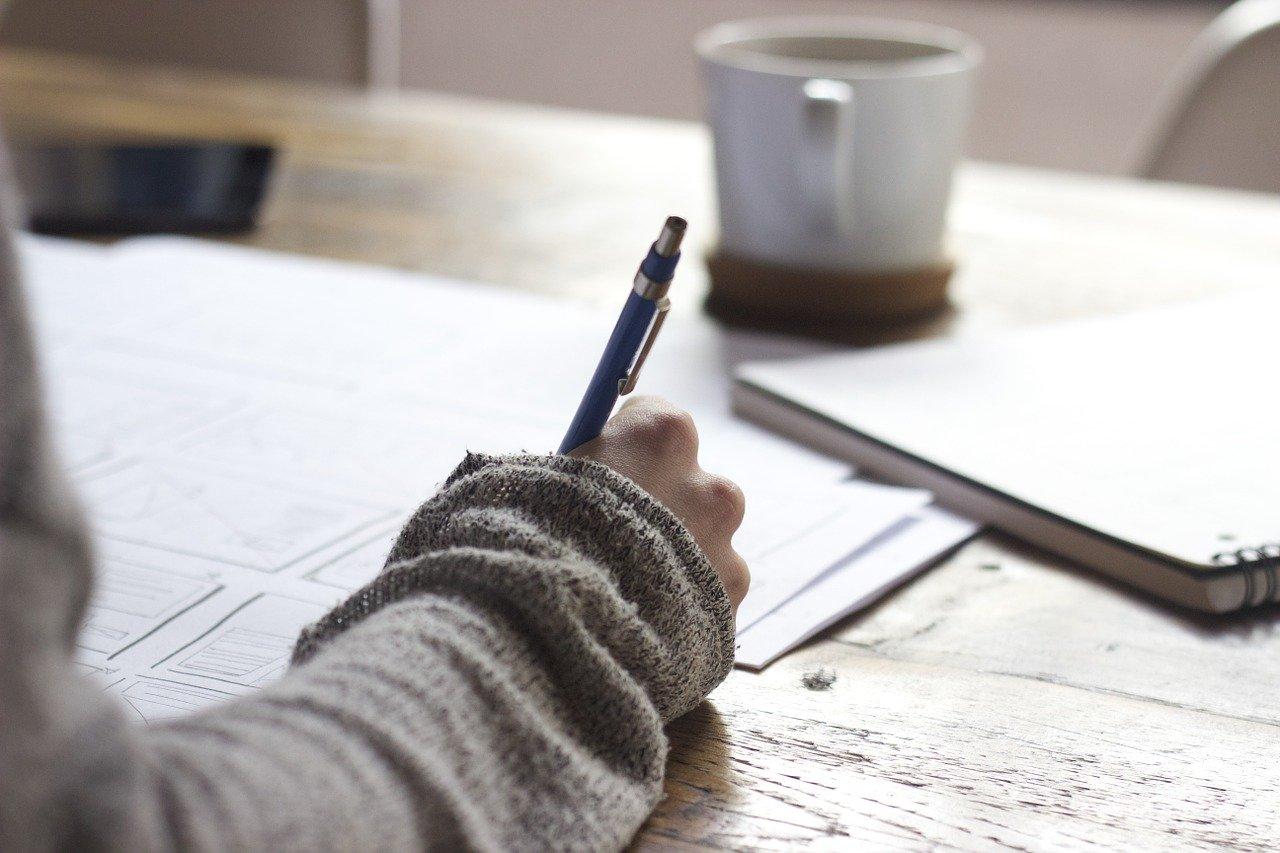 Mujer escribe notas mientras toma un café