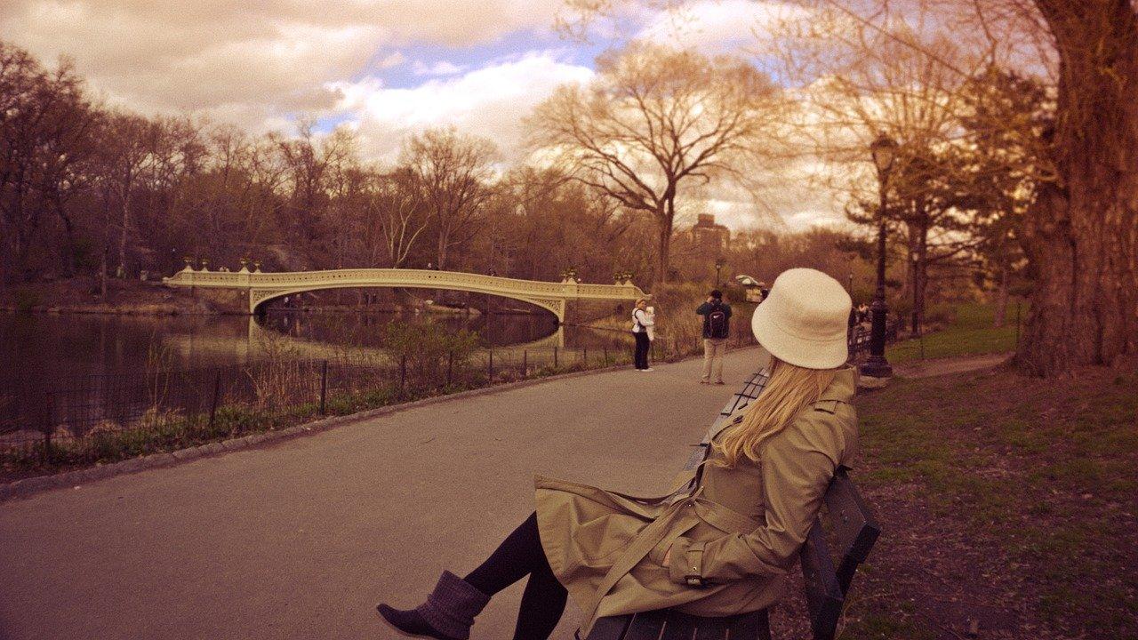 Una mujer sentada en un banco en un parque mira hacia el lago
