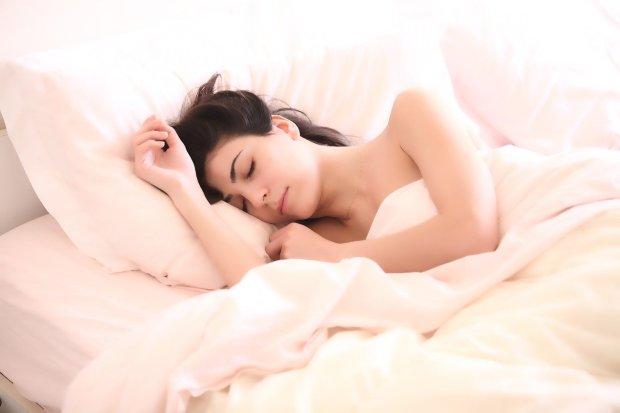 Mujer durmiendo en la cama, tal vez soñando